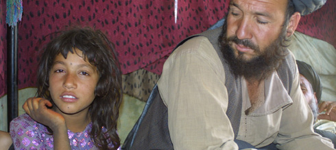 Guljumma, seven years old, with her father Wakil Tawos Khan, at the Helmand Refugee Camp District 5 in Kabul on August 31, 2009. Last year, an air attack by the US military struck their home in Afghanistan's Helmand Province. She lost an arm in the bombing. (Photo: Reese Erlich)