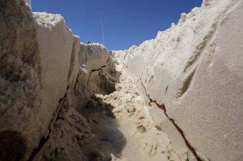 "Oil layer 6"" beneath sand surface"
